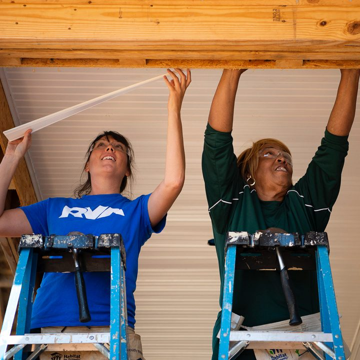 Two women install ceiling trim