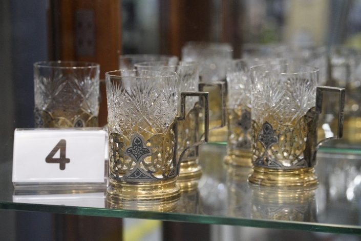 Glass steins with metal decoration and handle.