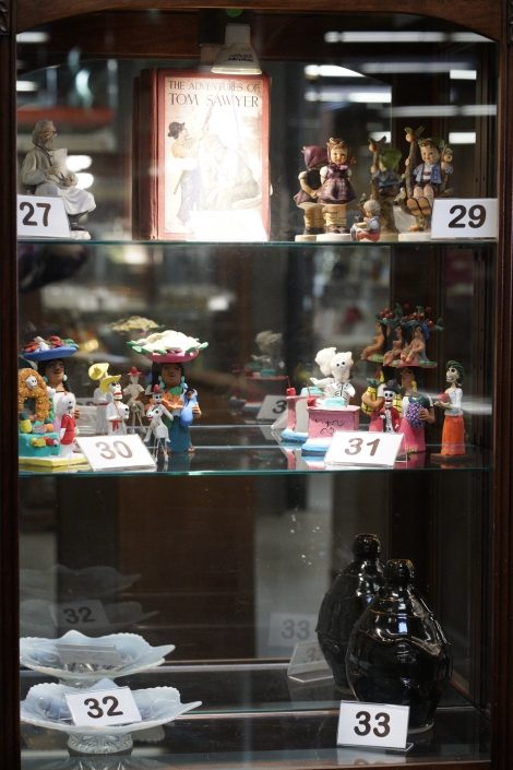 Collection of auction items: old book, display dishes, vase, and figurines.